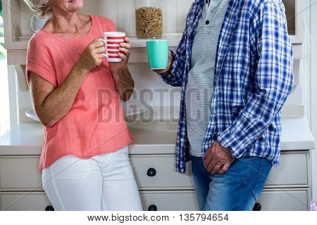 Midsection of senior couple having coffee in kitchen at home