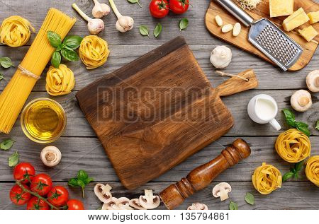 Spaghetti and fettuccine with different ingredients for cooking pasta on wooden table with blank of wooden kitchen board top view. Rustic style. Flat lay