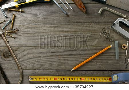 Frame with vintage tools on a wooden table in the workshop top view