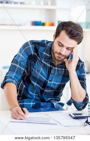 A man is concentrating on his notes at home