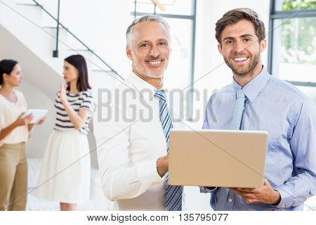 Two businessmen are smiling, posing and holding a laptop with on a background two women who are talking