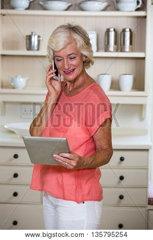 Senior woman holding digital tablet while talking on mobile phone in kitchen