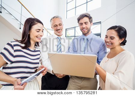 Smiling business people using laptop and tablet in office