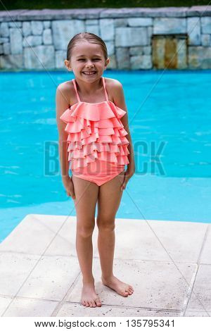 Happy girl standing by swimming pool