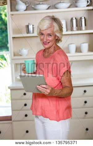 Portrait of senior woman using digital tablet while having coffee in kitchen