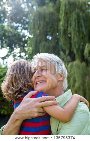 Happy grandfather hugging grandson at back yard