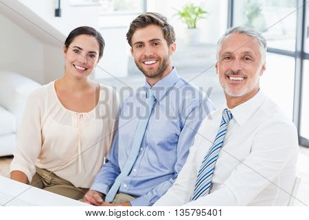 Portrait of business colleagues sitting at desk in office