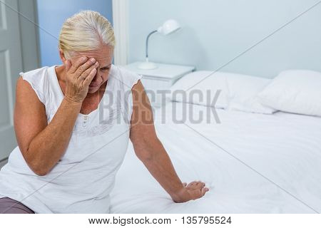 Upset senior woman touching head on bed at home