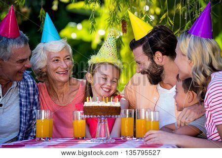 Happy family celebrating birthday of girl at yard