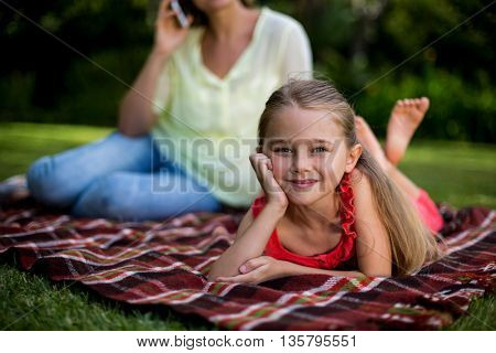 Close-up of girl lying on blanket while mother sitting in background