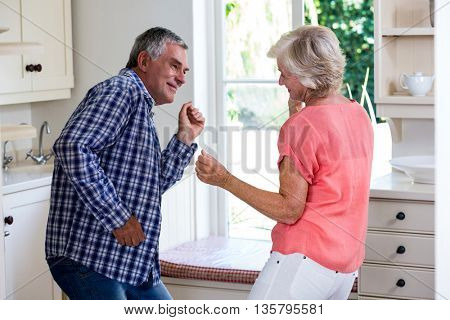Playful senior couple dancing in kitchen at home