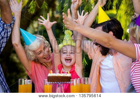 Cheerful multi- generation family celebrating birthday at yard