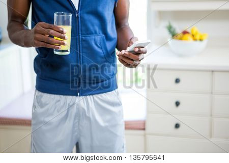 Mid- section of man holding a glass of juice while text messaging on phone at home