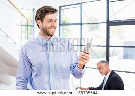 Businessman texting a message on phone in office
