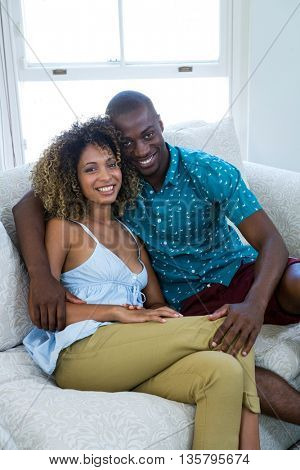 Young couple embracing while sitting on sofa at home