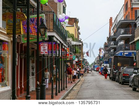 NEW ORLEANS, USA - MAY 14, 2015: Bourbon Street in French Quarter with pedestrians on the sidewalks and cars parked on the curb.
