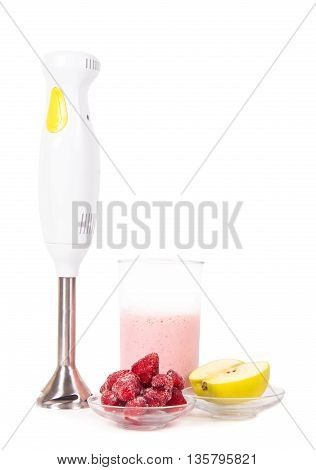 blender with the frozen fruits on white