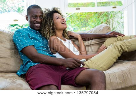 Happy young couple watching television in living room