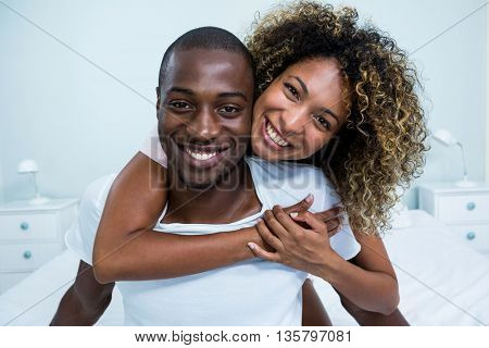 Young couple embracing each other on bed in bedroom