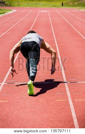 Rear view of athlete running on the running track on a sunny day