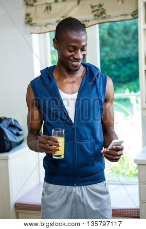 Young man holding a glass of juice while text messaging on phone at home