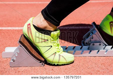 Close-up of athletes hands on a starting block about to run