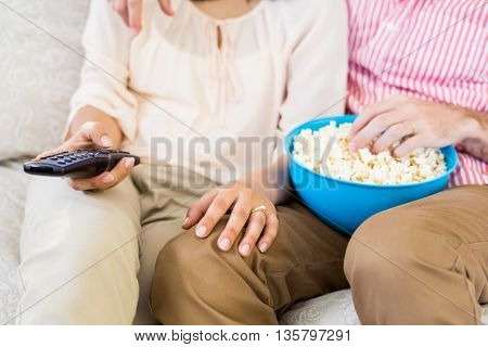 Mid section of couple sitting on sofa watching television and having popcorn