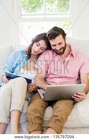 Couple using digital tablet and laptop in living room