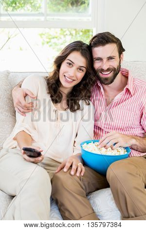 Couple sitting on sofa watching television and having popcorn
