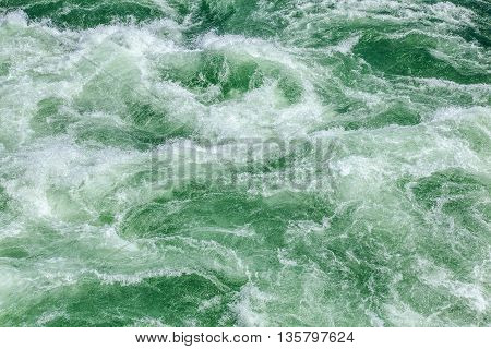 Green streaming water of a mountain river with white foam background/texture.
