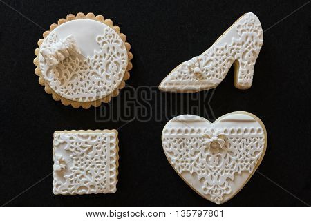 Homemade white butter cookies in various shapes on black background