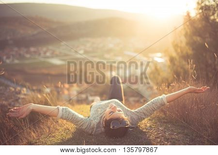 Carefree happy woman lying on green grass meadow on top of mountain edge cliff enjoying sun on her face.Enjoying nature sunset.Freedom.Enjoyment.Relaxing in mountains at sunrise.Sunshine.Daydreaming