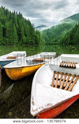 Mountain lake boats on cloudy day .
