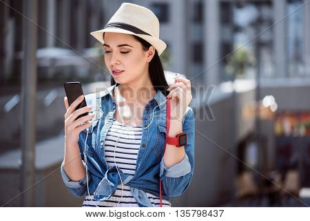 New generation, Pleasant beautiful glad woman holding cell phone and listening to music while having a walk