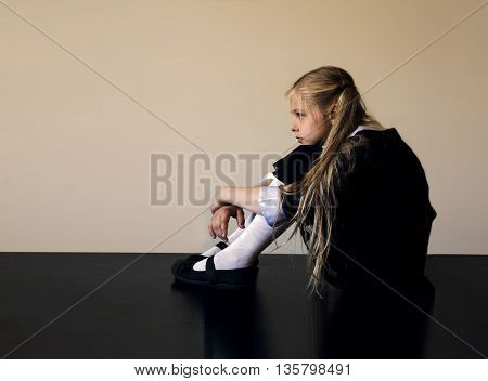 thoughtful cute little girl with long blond hair sitting on the floor
