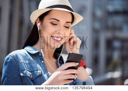 Active way of life. Cheerful delighted smiling young woman holding cell phone and listening to music while having a walk