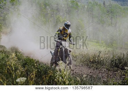racer a motorcyclist rides along a dusty forest trail during a race Enduro