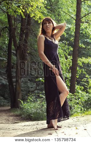Beautiful woman in sundress in sunny summer forest