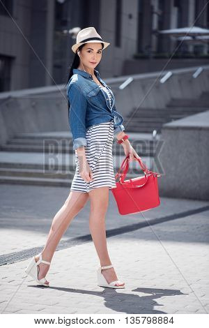 Have a nice day. Cheerful charming smiling woman listening to music and resting while having a walk
