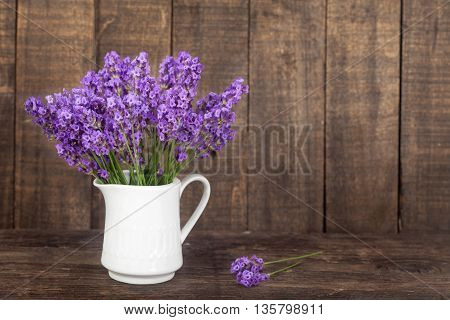 Bouquet of lavender flowers in a white porcelain jug on wooden background
