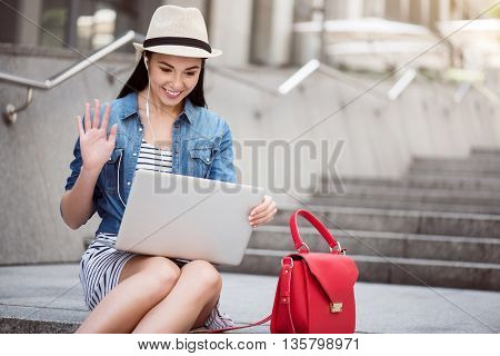 Nice to talk with you. Cheerful charming smiling woman using laptop and talking through the internet while sitting on the footsteps