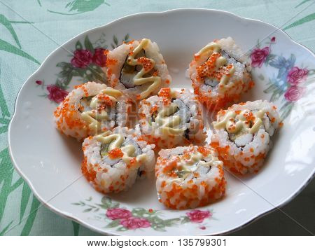 Uramaki sushi rainbow rolls with red caviar roe outer coating.