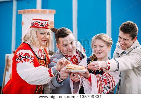 Gomel, Belarus - March 12, 2016: People dressed in national folk clothes posing with a plate of pancakes in hands at traditional folk Celebration of Maslenitsa Shrovetide holiday