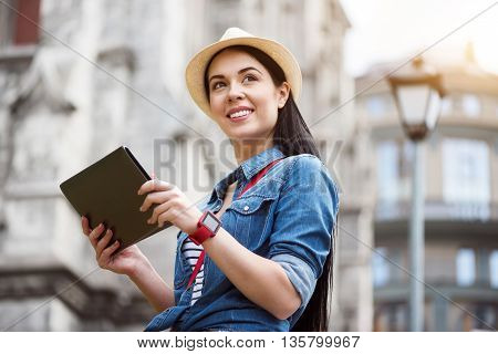 Modern view. Pleasant delighted positive woman holding tablet and looking aside while having a walk