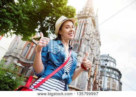 Life is great. Overjoyed smiling beautiful woman thumbing up and standing in the street while having a walk