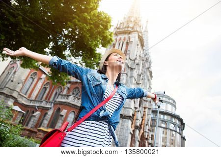 Enjoy every day. Positive delighted smiling young woman holding hands aside and feeling content while having a walk