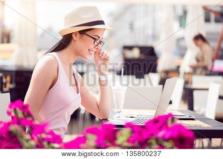 Pleasant day. Nice beautiful cheerful woman sitting at the table and using laptop while resting in the cafe