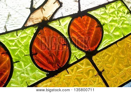 Red leaves in stained glass window. Abstract geometric colorful background. Multicolored stained glass church window with irregular random block pattern.
