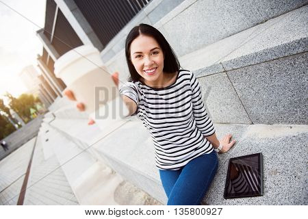 That is for you. Cheerful smiling charming woman sitting on the footsteps and drinking coffee while giving it to you