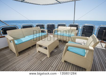 Table And Chairs On Deck Of A Luxury Motor Yacht